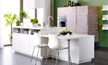 Des lignes sobres pour les meubles d'une cuisine blanche offrant une ouverture sur le salon à la fois conviviale et pratique. Côté cuisine, l'îlot intègre l'évier, coté salon il sert au rangement de la vaisselle. Le plan de travail sur un 2eme niveau se transforme en table à l'heure des repas.