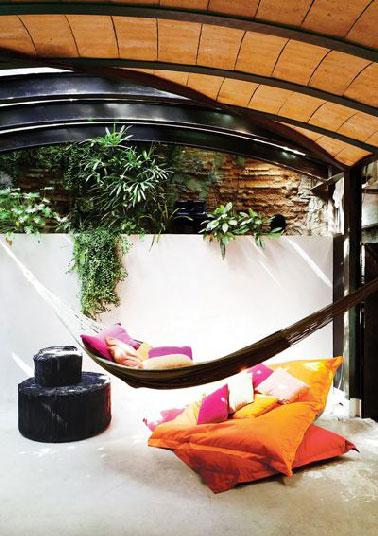 Les auteurs de la décoration de cette terrasse avait sûrement en tête la destination première d'une terrasse : la détente absolue. Pas étonnant, que hamac, big coussins de sol et jeux de cache cache avec le soleil soient réunis pour y arriver.