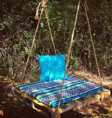 Une balancelle en palette au milieu du jardin pour se reposer tranquillement à l'ombre . Pour la faire, une palette, 4 cordes et des coussins de plage