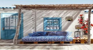 Du bleu et blanc en phase avec l'ambiance bord de mer, palettes bois et canisses se chargent de la banquette et de filtrer les rayons du soleil. Astucieuse, la table en bout de canapé réalisée elle aussi avec des palettes.