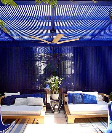 Abritée du soleil et du vent sous un patio construit en bois peint en bleu, une terrasse design aménagée avec de larges bains bain de soleil en bois et toile blanche.