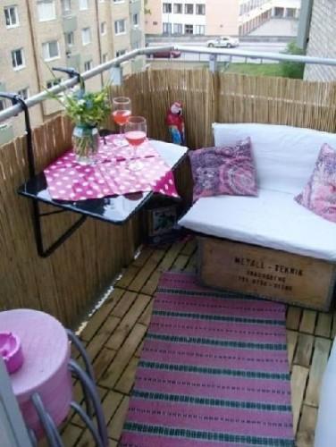 Intimité assurée sur le balcon grâce à du canisse et un sol en caillebotis pour s'aménager un espace extérieur rien qu'à soi.  Pour l'aspect déco, coussins, tapis, set de table de couleur flashy et la détente peut commencer.
