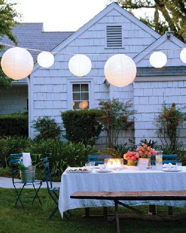 Une guirlande électrique fabriquée avec des boules japonaises suspendue au dessus de la table de jardin ça peut rester installer tout l'été.