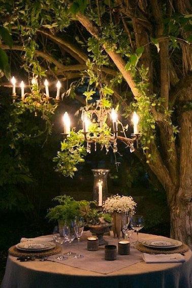 Quoi de plus romantique qu'un dîner en tête à tête dans le jardin que de suspendre 2 lustres dans un arbre et d'avoir un photophore sur la table ronde !