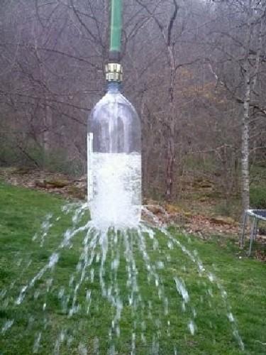Il fallait y penser ! installer une douche d'extérieur avec une bouteille plastique transformée en pommeau et fixée au bout du tuyau d'arrosage suspendu à un arbre. une idée futée pour se rafraichir sous une douche de jardin construite avec les moyens du bord !