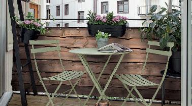 Un aménagement coquet sur le balcon qui assure l'intimité grâce à des planches de bois fixées sur la rambarde et un parquet bois exotique pour leur faire écho.