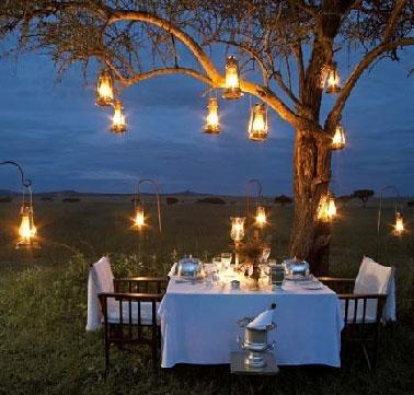 Pour organiser un dîner champêtre convivial, éclairer la table de jardin et la zone du terrain autour avec une multitude de lampes à pétrole crée une ambiance chaleureuse, et si un arbre se fait complice pour aider à suspendre les lampes c'est génial.