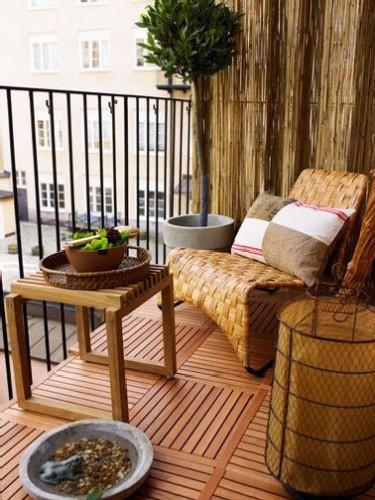 Une ambiance chaleureuse se dégage sur ce balcon aménagé tout en bois. Dalles, canisse et mobilier en rotin dans la même tonalité de blond doré.