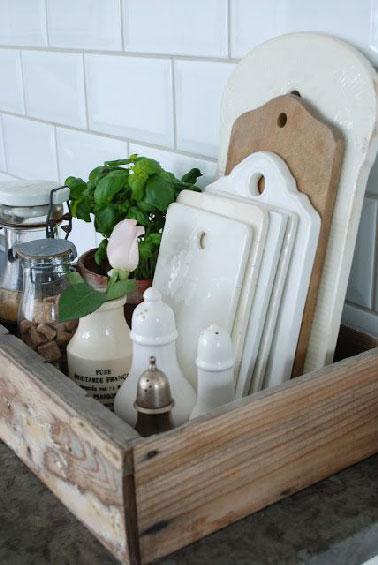 Une astuce pas chère pour ranger les planches à découper dans la cuisine avec une caisse à vin. Selon le nombre de planches, salière, poivrière et bocaux trouvent une place aussi dans la caisse.