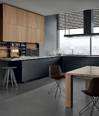 Dans un appartement moderne juché au dernier étage d'une résidence espagnole, une grande cuisine allie noir et bois pour un rendu exceptionnel.  Contrastant avec les meubles bas noir mat, un plan de travail en Corian du même gris que le pan de mur et le sol.
