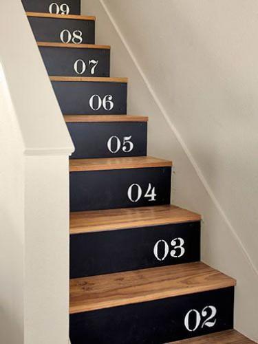 Un relooking d'escalier en bois fait sur le mode ludique avec les marches revernies et contremarches peintes en noir avec pochoir chiffre blanc.
