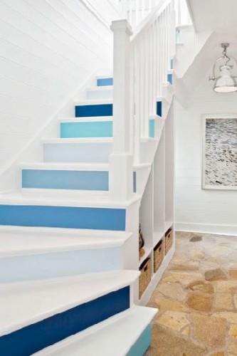 Combiner rangement sous escalier pratique et esthétique, c'est ce que réussi cet escalier peint en blanc avec un dégradé de peinture bleu sur les contremarche pour une mise en couleur discrète.