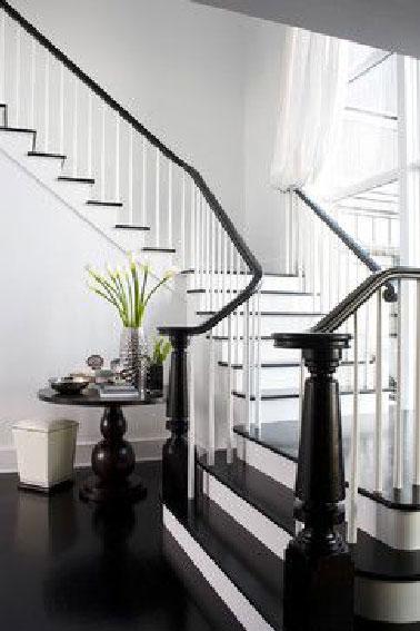 Majestueuse, grandiose la déco d'un grand escalier d'une maison ancienne peint en noir pour former un prolongement avec le sol de l'entrée. Une charmante déco modernisée en noir et blanc.