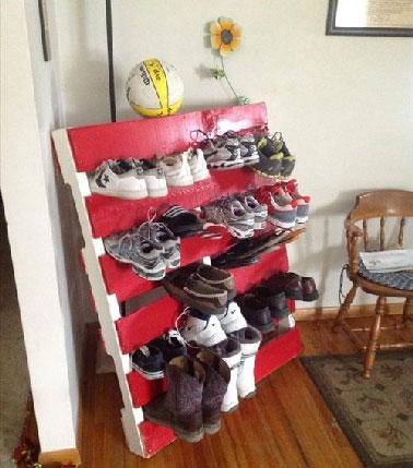 Un aménagement de studio astucieux avec un rangement des chaussures glissées dans une palette bois peinte en rouge et blanc