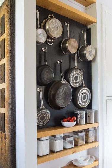 Voilà une astuce pour le rangement des casseroles et bocaux dans une cuisine qui manque de placards. Dans un renfoncement, casseroles  et bocaux trouvent leur place sur les étagères en teck.