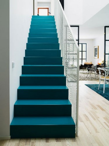Trop beau cet escalier recouvert d'une peinture bleu canard dans le séjour blanc et noir d'une maison scandinave. Coup de coeur de la rédac de Déco Cool pour cet escalier lumineux.