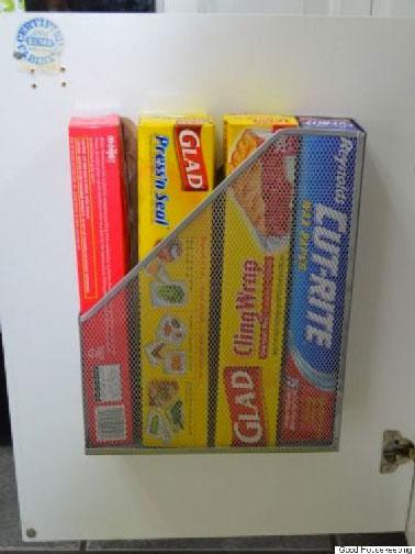 Une idée pratique pour résoudre la désorganisation du rangement des rouleaux d'alu et film alimentaire : un classeur en guise de panier fixé à l'intérieur d'un meuble de cuisine.