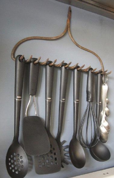 Conjuguer déco récup et organisation du rangement de la cuisine avec un râteau pour suspendre les spatules au dessus de la cuisinière, une astuce déco pas chère.