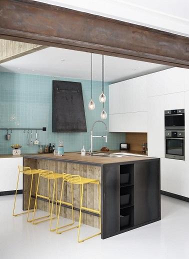 Cette cuisine de style industriel est à la pointe de la tendance avec son mur bleu et ses tabourets jaunes. L'ilot central quant à lui structure la pièce.
