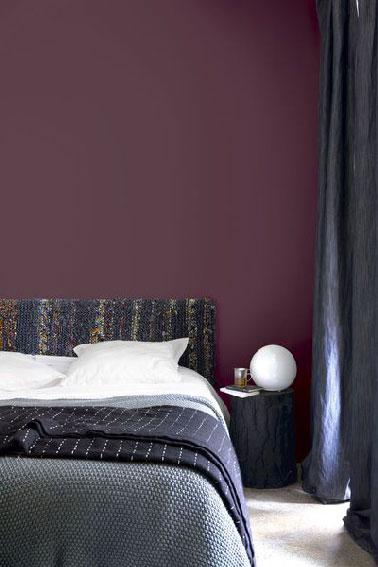 Aubergine ou le chic d'une couleur foncée pour faire la décoration de sa chambre. Mur de la tête de lit peint couleur aubergine, camaïeux de bleupour les coussins et linge de lit  et la chambre s'enveloppe d'une ambiance paisible.