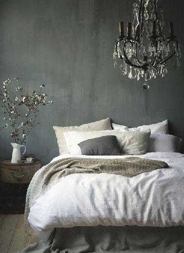 Un lustre noir pour inscrire la déco d'une chambre dans un style baroque. Autour des murs gris anthracite et des tons lin du linge de lit c il assure l'originalité sans toutefois éclairer la pièce de manière à préserver l'ambiance cosy de la chambre.