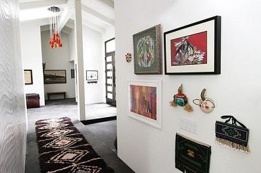 Une déco couloir style ethnique peut aussi être moderne. Les cadres, les objets accrochés au murs et le tapis le prouvent grâce à des couleurs modernes.