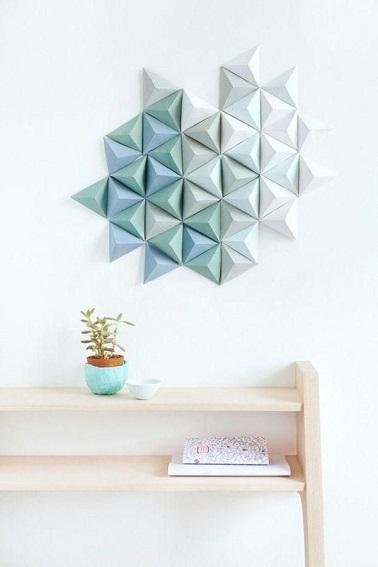 Un nuage d'origamis s'est collé sur ce mur offrant une déco en relief unique dans la tendance des formes géométriques. Une idée facile à refaire chez soi !