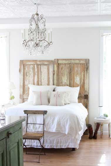 La simplicité se fait chic dans une chambre blanche avec une tête de lit aménagée avec 2 portes aspect bois flotté posées à la tête du lit sans autres transformations. Point d'orgue pour un style bohème chic, le lustre à facettes en verre blanc.
