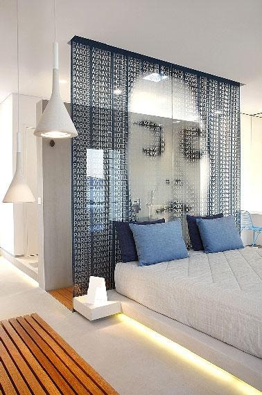 Une suite parentale de 45 m2  à vous faire rêver d'évasion à Athènes. Aménagée par l'agenceA31 architecte, cette chambre luxueuse dissimule derrière la cloison de verre installée à la tête du lit, une douche italienne aux murs enduits de ciment clair sublimant le sol et receveur en teck.