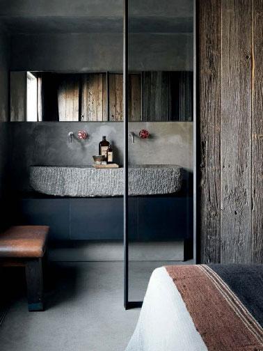 Une décoration de petite chambre parentale qui réussit le pari de mixer les styles dans une parfaite harmonie. L'aspect rustique apporté par le lieux lui même, une grande réaménagée, une touche moderne avec le meuble noir et l'authenticité de la vasque en pierre.