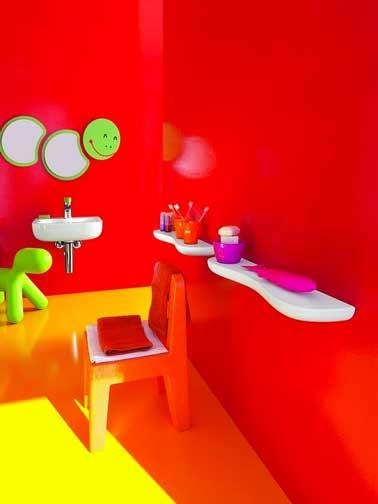 Une déco couleur salle de bain qui donne aux enfants une dose de bonne humeur dès la toilette du matin. Un rouge brillant sur les murs, jaunes sur le sol et du vert anis avec un miroir rigolo et un chien gonflable Fatboy