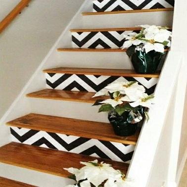 Cet escalier déco surfe sur la tendance graphique avec ses motifs chevrons peint. Pour un escalier moderne, optez pour du noir et blanc chic et élégant.