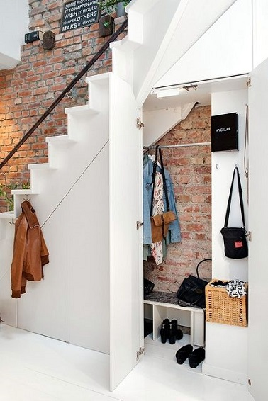 Dans cette entrée, l'espace sous l'escalier est un rangement utile pour se débarrasser de ses affaires discrètement. Comme un mini dressing, ce rangement est très pratique.