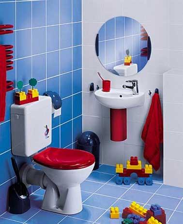 Des couleurs déco idéales pour une salle de bain ludique pour enfant en bas âge. S'inspirant des couleurs des Légo, un carrelage bleu et blanc en mural et sol, abattant de WC et accessoires de toilette rouge vif autour d'éléments sanitaires aménagées à sa taille.