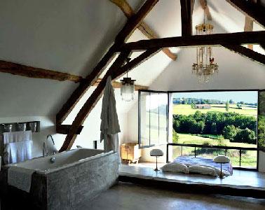 Une vue panoramique de rêve depuis le lit de cette chambre parentale relevé de quelques centimètre par l'estrade. La baignoire îlot installée dans la seconde partie de la chambre invite à la détente.