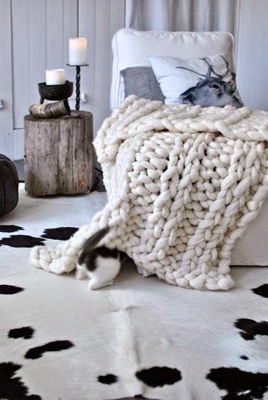 Idée déco pour une chambre au top du cocooning : opter pour un plaid en laine grosse maille. Ce dernier décore la pièce en donnant de la chaleur et vous réchauffe l'hiver.