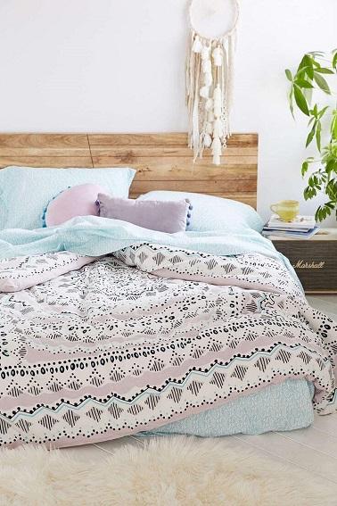Des couleurs pastel sur le linge de lit et un cadre en bois, cette chambre à tout d'une pièce cocooning. Le tapis fourrure au sol renforce l'effet confort nid douillet.