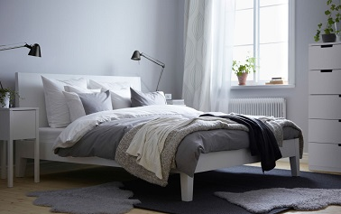 Dans une chambre déco cocooning, la multiplication de coussins et de plaids en nuances de gris en fait un nid douillet comme jamais. Et les tapis réchauffent la pièce.
