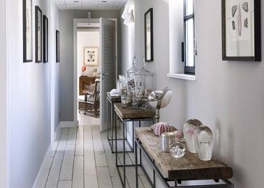 Cette déco couloir met en avant un style galerie d'art avec des console en bois rustiques et des objets déco en tout genre.
