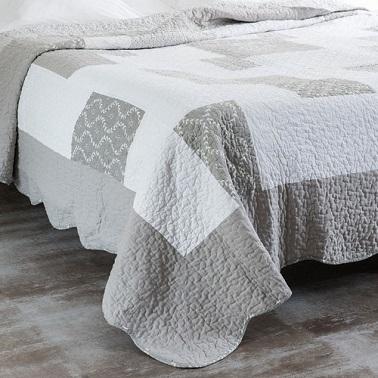 Couleur gris et blanc pour un boutis chaleureux sur le lit d'une chambre cocon