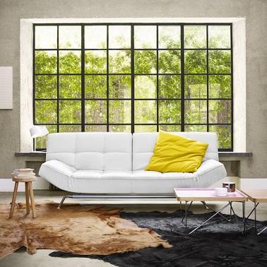Design, ce salon lumineux avec une grande baie vitrée met en valeur un canapé blanc à la forme moderne. Modulables le dossier et les accoudoirs se baissent et se relèvent.