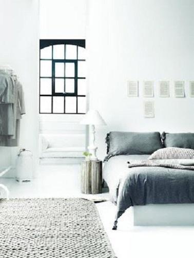 Dans une chambre blanche, le gris sur un tapis en maille ou un ensemble de linge de lit donne du caractère à la pièce et un contour de fenêtre noir apporte un effet design.