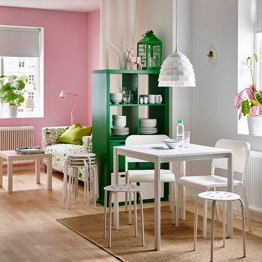 Une cloison peut aussi être discrète. Une étagère et un rideau font l'affaire pour décorer et agencer intelligemment l'espace en créant un coin repas et un salon distincts.