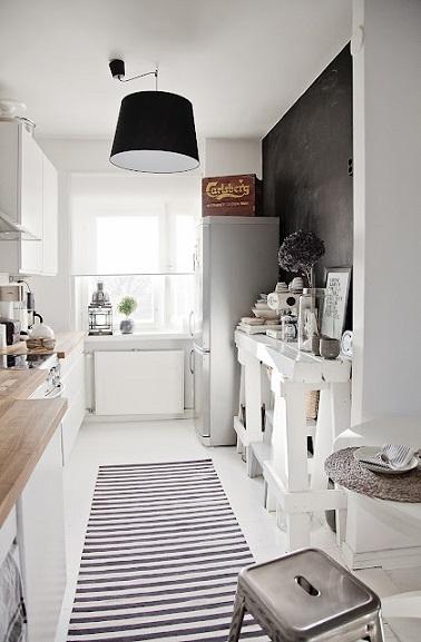 Dans cette cuisine toute en longueur, mettre un tapis aux rayures horizontales au sol donne l'illusion d'un espace plus large. En noir et blanc ça rompt l'effet couloir.