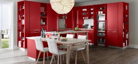 Une cuisine complètement ouverte et rouge avec de grands meubles pratiques.