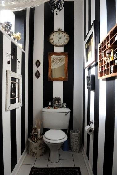 Non seulement ces WC osent le noir, mais ils vont même jusqu'à utiliser un papier peint vinyle à rayures verticales. Une déco originale pleine de charme et de contraste !