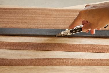 Pour réaliser le décor du sapin de Noël en bois, découper à l'aide d'un cutter des formes dans des feuilles de placage de différentes essences pour encore plus d'effet.