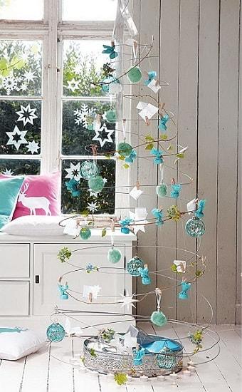 Presque invisible, ce sapin de Noël original en fil de fer en forme de torsade est décoré avec des éléments bleus et blancs pour une esthétique très aérienne.