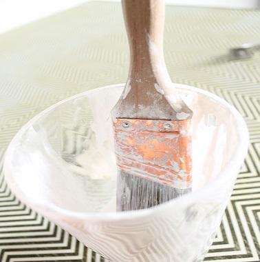 Après avoir nettoyé et poncé le bureau, on le repeint en appliquant une peinture blanche spécial fer pour lisser la surface.