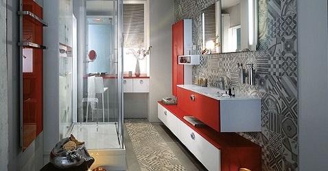 Une salle de bain design qui mélange carreaux de ciment aux murs et au sol avec des meubles rouges.